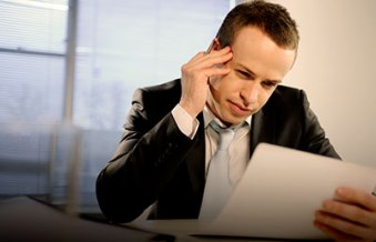 Businessman-Reviewing-Document-Thinking-Hard(1)